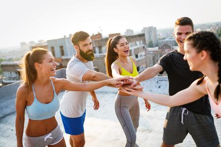Photo pour Group of happy fit friends exercising outdoor in city - image libre de droit