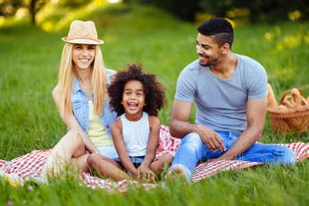 Photo pour Picture of lovely couple with their daughter having picnic - image libre de droit