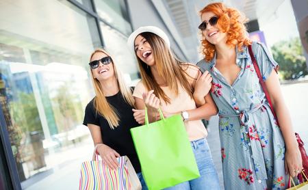 Photo pour Group of happy smiling friends shopping in the city - image libre de droit
