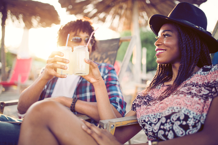 Photo pour Happy black couple on the beach while relaxing on their deck chairs - image libre de droit