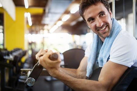 Photo pour Young fit handsome man doing exercises in gym - image libre de droit