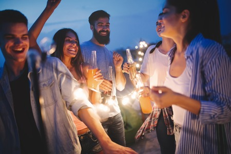 Photo for Happy friends with drinks toasting at rooftop party at night - Royalty Free Image