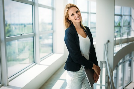 Photo for Portrait of young busineswoman standing in office lobby. - Royalty Free Image