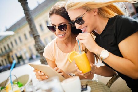 Photo pour Beautiful girls having fun smiling together in a cafe outdoor - image libre de droit