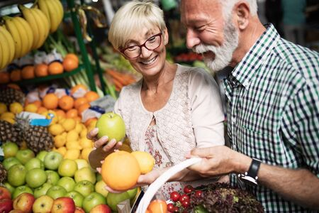 Foto per Portrait of beautiful elderly couple in market buing food - Immagine Royalty Free