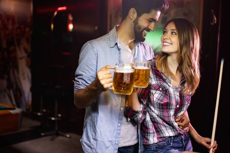 Photo pour Couple drinking beer and playing snooker on date - image libre de droit