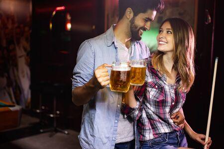 Foto de Couple drinking beer and playing snooker on date - Imagen libre de derechos