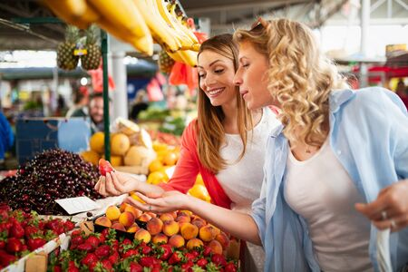 Photo for Young happy women shopping vegetables and fruits on the market - Royalty Free Image
