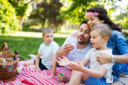 Photo pour Family with children blow soap bubbles outdoors - image libre de droit