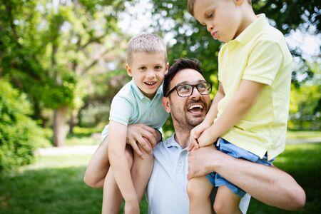 Photo pour Father carrying his children and smiling outdoors - image libre de droit