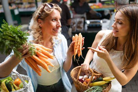 Photo pour Young happy women shopping vegetables and fruits on the market - image libre de droit