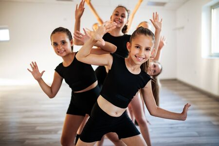 Foto de Group of fit happy children exercising ballet in studio together - Imagen libre de derechos