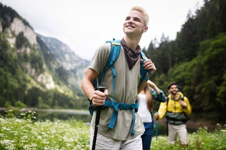 Photo pour Group of happy friends with backpacks hiking together - image libre de droit