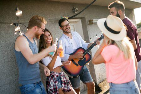 Photo pour Group of happy friends having party on rooftop - image libre de droit