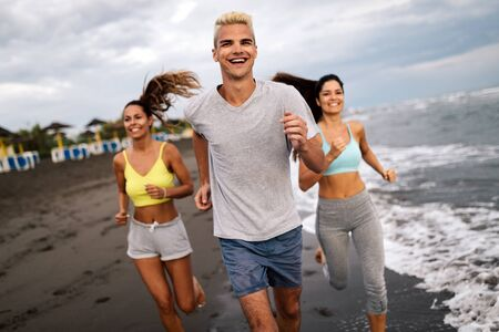 Photo for Group of people, friends running on the beach at sunset - Royalty Free Image