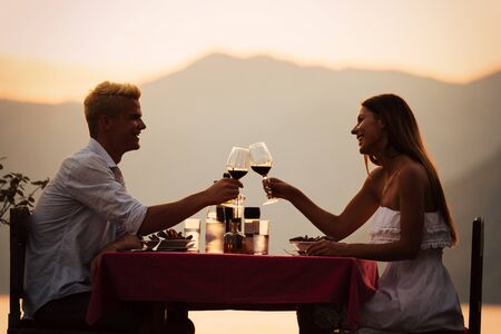 Foto de People, vacation, love and romance concept. Young couple enjoying a romantic dinner on beach. - Imagen libre de derechos