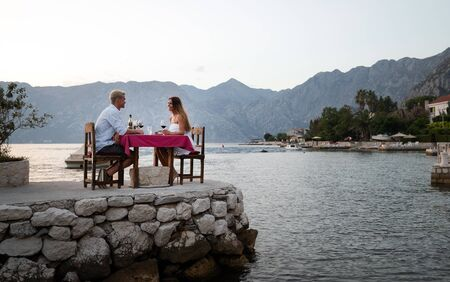 Photo pour Couple is having a private event dinner on a tropical beach during sunset time - image libre de droit