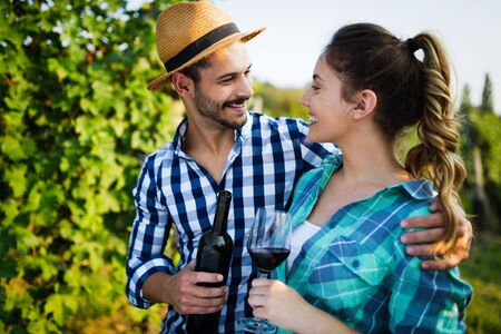 Photo for Young wine growers tasting wine in vineyard - Royalty Free Image