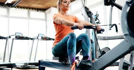 Photo pour Workout woman cross training exercising cardio using rowing machine - image libre de droit
