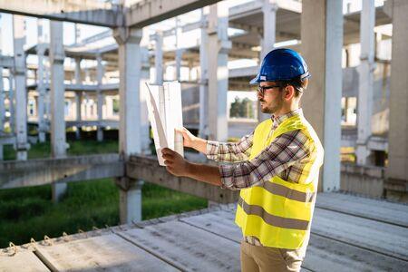 Photo pour Engineer working on construction site and holding blueprint - image libre de droit