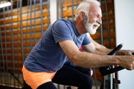 Photo pour Mature fit people biking in the gym, exercising legs doing cardio workout cycling bikes - image libre de droit