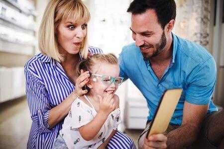 Photo pour Happy family choosing glasses in optics store - image libre de droit