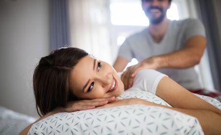 Photo pour Cheerful young couple making massage at home - image libre de droit