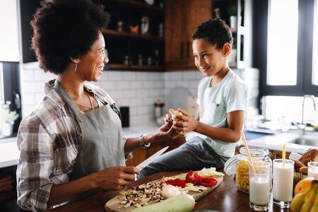 Photo pour Mother and child having fun preparing healthy food in kitchen - image libre de droit