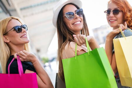 Photo pour Happiness, friends, shopping and fun concept-smiling young women with shopping bags. - image libre de droit