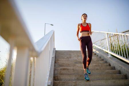 Foto de Portrait of fit cheerful woman resting after a run in a city - Imagen libre de derechos