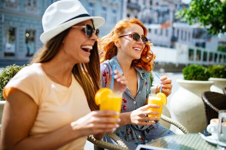 Photo for Friends having a great time in cafe. Women smiling and drinking juice and enjoying together - Royalty Free Image