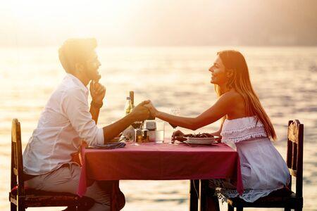 Foto de People, vacation, love and romance concept. Young couple enjoying a romantic dinner on beach. - Imagen libre de derechos