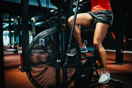 Photo pour Fitness female using air bike for cardio workout at crossfit gym. - image libre de droit