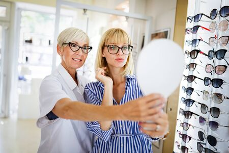 Photo pour Health care, people, eyesight and vision concept. Woman with optician choosing glasses - image libre de droit