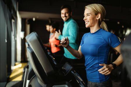 Foto de People running on treadmill in gym doing cardio workout - Imagen libre de derechos