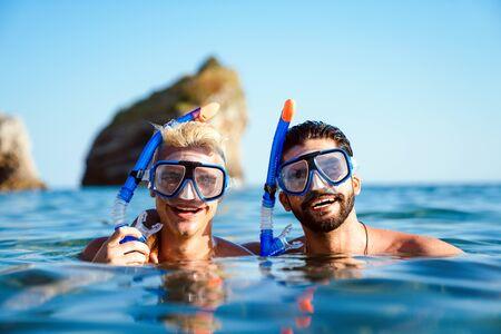 Photo pour Happy friends men enjoying summer vacation and scuba diving - image libre de droit