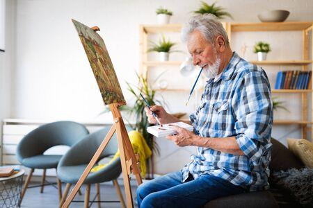 Foto de Happy retired man painting on canvas for fun at home - Imagen libre de derechos