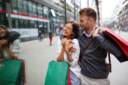 Photo for Cheerful successful happy young lovely couple with shopping bags traveling and laughing - Royalty Free Image