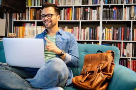 Photo pour Smiling male student working and studying in a library - image libre de droit