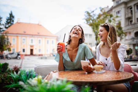 Photo pour Technology, friendship and people concept. Happy young women with smartphone at outdoor cafe - image libre de droit