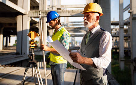 Photo pour Two satisfied engineers talking at building site with construction structure in background - image libre de droit