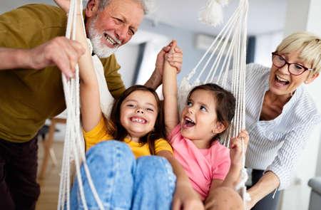 Photo pour Happy grandparents having fun times with children at home - image libre de droit
