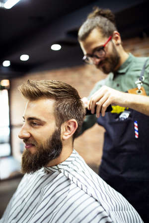 Foto für Young bearded man getting haircut by hairdresser while sitting in chair at barbershop - Lizenzfreies Bild