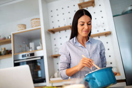Photo for Beautiful young woman is preparing food in kitchen at home. Healthy food, diet concept - Royalty Free Image