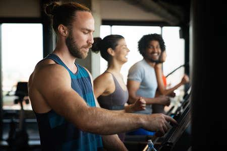 Foto de Group of young people running on treadmills in sport gym - Imagen libre de derechos