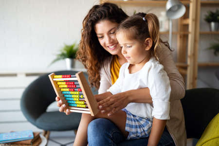 Photo pour Mother and little cute girl, kid playing with abacus, early education - image libre de droit