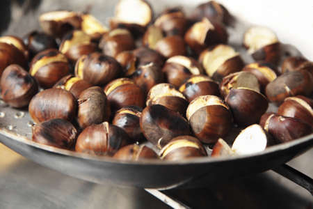 Chestnuts being roasted in a special pan with holes