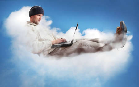 Foto de A man on a cloud operating a laptop.  The man is dressed casually to represent the majority of IT workers.  The concept is Cloud Computing - software/computing in the cloud. - Imagen libre de derechos
