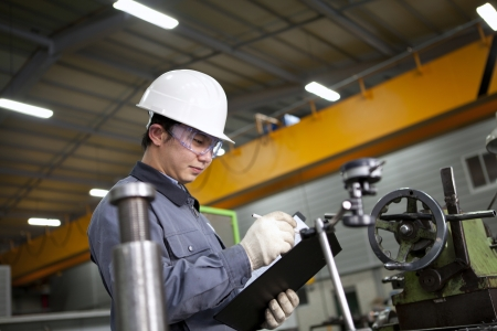 Photo for mechanical technician writing on notepad in the factory - Royalty Free Image