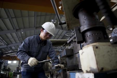 mechanical technician measuring detail after cnc